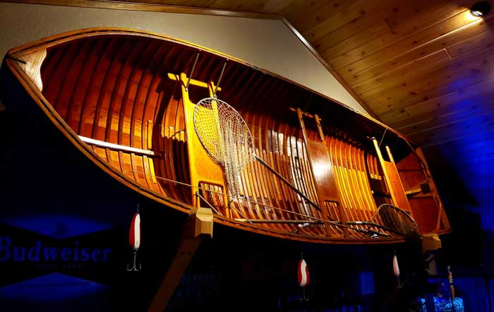 A beautiful hand-crafted row boat adorns the wall in The Olde Cedar Inn